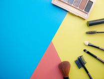 Makeup and makeup brushes, eye shadows on a colored background. Cosmetics for the face. With empty space on the left stock photos
