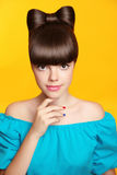 Makeup. Manicure. Beautiful smiling teen girl with bow hairstyle. And multicolor manicured polish nails. Funny girl showing fingers isolated on yellow Stock Photo