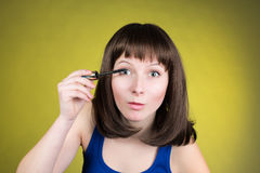 Makeup mascara woman getting ready looking in camera as in a mirror. Funny image of beautiful trendy young female fashion model. Stock Image