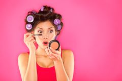 Makeup mascara woman with hair rollers. Getting ready looking in pocket mirror. Funny image of beautiful funky trendy young mixed race asian caucasian female Royalty Free Stock Image