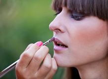 Makeup master applying lipstick Stock Photography