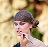 Makeup master applying lipstick Royalty Free Stock Image