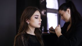 Makeup master increases eyelashes, make up artist making long lashes, woman in beauty studio makes evening make up. Beautiful caucasian girl with finished stock video