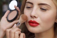 Makeup master paint a beautiful young girl closeup Stock Image