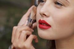 Makeup master paint a beautiful young girl closeup Stock Photo