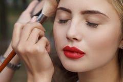 Makeup master paint a beautiful young girl closeup Stock Photography