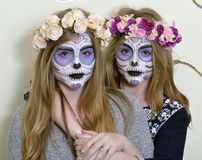 Makeup Mexican death mask. Halloween two blonde girls with makeup Mexican death mask and with a wreath of flowers Stock Photo
