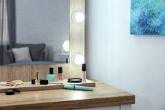 Makeup mirror on table near white wall. In dressing room stock image