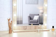 Makeup mirror on table near white wall in room. Makeup mirror on table near white wall in dressing room royalty free stock photo