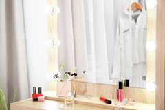 Makeup mirror on table near white wall in dressing room. Space for text royalty free stock photo
