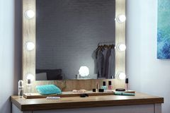 Makeup mirror on table near white wall. In dressing room stock photo