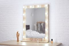 Makeup mirror on table near white wall. In dressing room stock photography