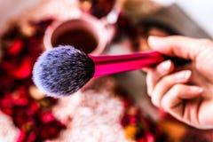 Makeup muśnięcie w femle ręce na pięknym zamazanym tle Osoba widok zdjęcie stock