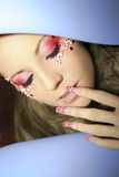 Makeup and nail red color. A young girl in a flower makeup and nail red color royalty free stock image
