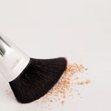 Makeup natural brush with beige powder Stock Photos