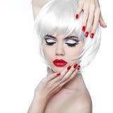 Makeup och frisyr. Röda kanter och Manicured spikar. Modefriare Royaltyfri Bild