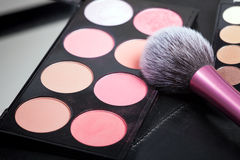 Makeup palets and brush on black lather. Stock Image