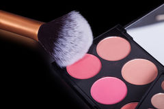 Makeup palets and brush on black lather. Stock Images