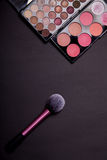 Makeup palets and brush on dark background. Stock Image