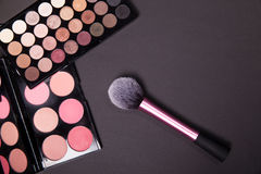 Makeup palets and brush on pure black background. Royalty Free Stock Image
