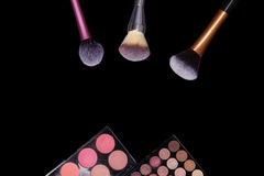 Makeup palets and brushes on pure black background. Stock Photography