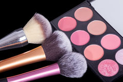 Makeup palets and brushes on pure black background. Stock Photos