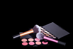 Makeup palets and brushes on pure black background. Royalty Free Stock Photography