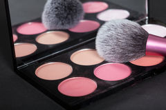 Makeup palets and closeup on brush on pure black background. Stock Photography