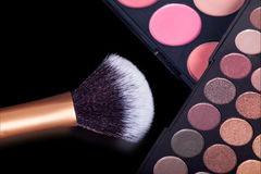 Makeup palets and closeup on brush on pure black background. Stock Image