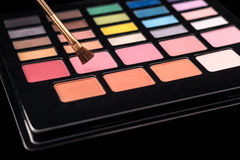 Makeup palette of colorful eyeshadows with makeup brush isolated Stock Photo