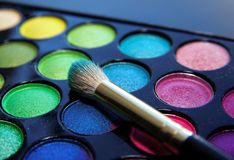 Makeup palette colors brush cosmetics. Make-up brush and eyeshadow palette over black close up Royalty Free Stock Photo