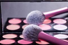 Makeup palette with makeup brush. Brush reflect in mirror. Stock Photos