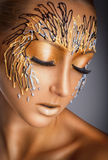 Makeup. Portrait of a beautiful woman with fantasy gold makeup on a gray background Royalty Free Stock Image