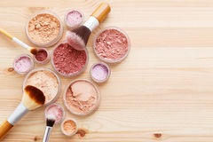 Makeup powder and brushes on wood background stock images
