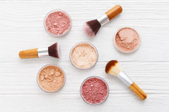 Makeup powder with brushes on wood background Stock Photo