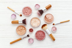 Makeup powder products with brushes flat lay. Makeup powder products with foundation blush eye shadow and brush on white wood background flat lay Stock Photos