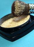 Makeup powders and brush on blue background Stock Photos