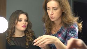 Makeup process, makeup artist using brush and compact powder and colors model at salon. Portrait of two beautiful women.  stock footage