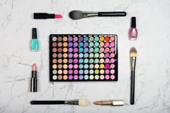 Makeup products arranged as frame around colorful eyeshadow palette on marble background. Flat lay royalty free stock image
