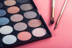 Makeup products brush and color palette. On pink background royalty free stock photography