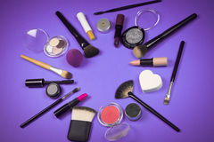 Makeup products. Different makeup products in circle on purple background Stock Photos