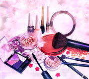 Makeup products and jewelry on floral background