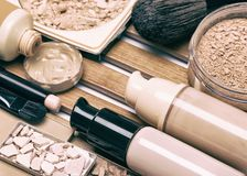 Makeup products for perfect complexion. Concealer, foundation and correcting, bronzing, highlighting powder with make up brushes. Toned image Stock Images