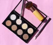 Makeup Palette for Highlight and Contour with Brushes on a Pink Surface stock images