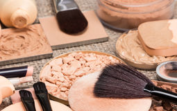 Makeup products to create the perfect complexion. Correctors, foundation, powder, bronzer with brushes and cosmetic sponges on sackcloth. Side view, shallow Royalty Free Stock Images