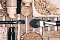 Makeup products to even skin tone and complexion. Corrector, loose, compact and bronzing powders, concealer pencil, liquid foundation with make up brushes Stock Image