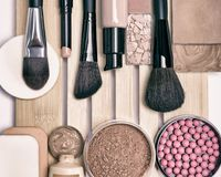 Makeup products to even skin tone and complexion. Essential makeup products and accessories to even out skin tone and complexion. Top view, toned in retro Stock Image