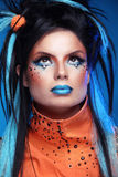 Makeup. Punk Hairstyle. Close up portrait of Rock girl with Blue. Lips and black Hair Styling with colored strand of hair Stock Photography