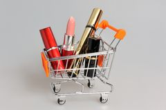 Makeup in pushcart on gray Stock Photos