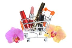 Makeup in pushcart with orchid flowers isolated Royalty Free Stock Images